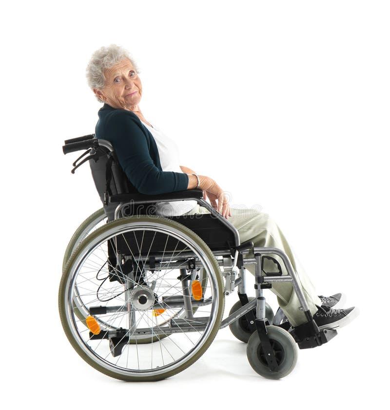 Hogere vrouw in rolstoel op witte achtergrond stock foto's