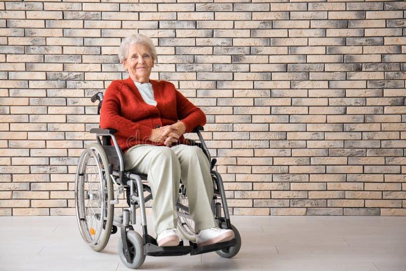 Hogere vrouw in rolstoel tegen bakstenen muur stock foto's