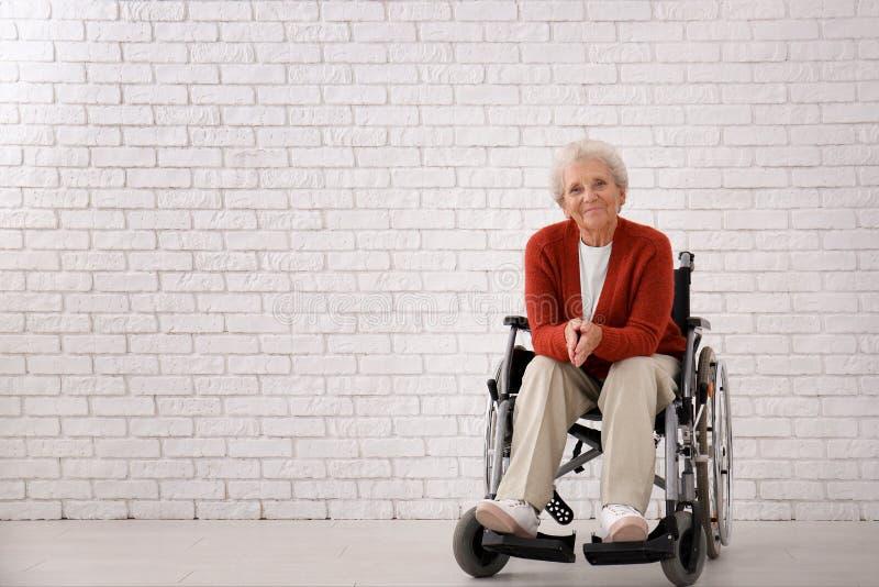 Hogere vrouw in rolstoel tegen witte bakstenen muur royalty-vrije stock foto's
