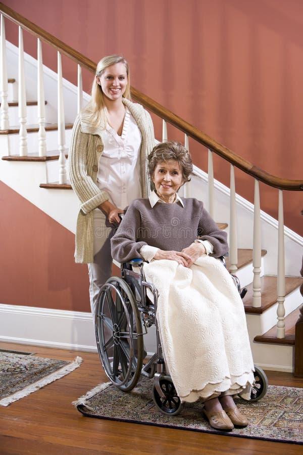 Hogere vrouw in rolstoel thuis met verpleegster stock fotografie
