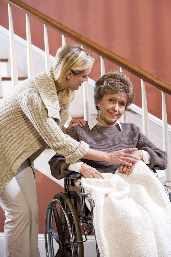 Hogere vrouw in rolstoel thuis met verpleegster royalty-vrije stock foto's