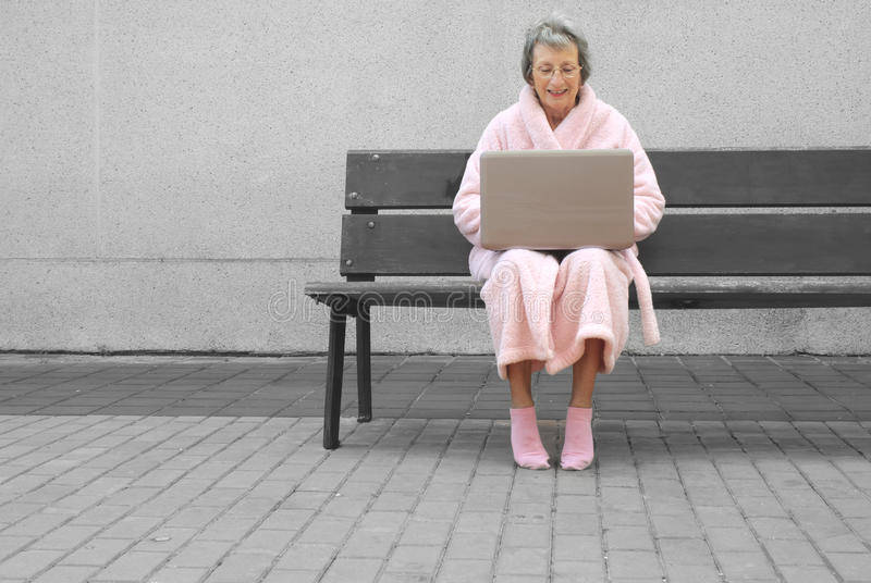 Hogere vrouw in roze robe in openlucht met laptop