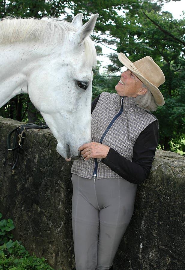 Hogere vrouw ruiter met paard stock foto's