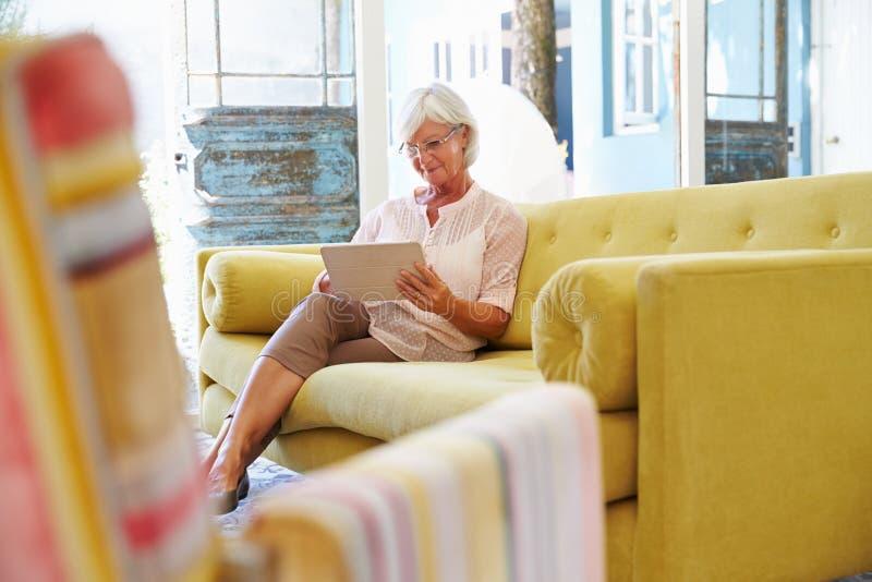 Hogere Vrouw thuis in Zitkamer die Digitale Tablet gebruiken royalty-vrije stock fotografie