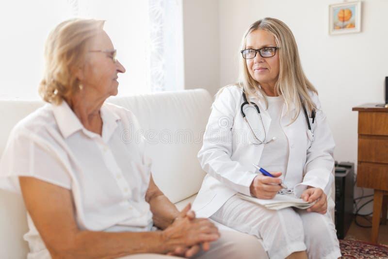 Hogere vrouw tijdens een medisch examen met vakman stock afbeelding
