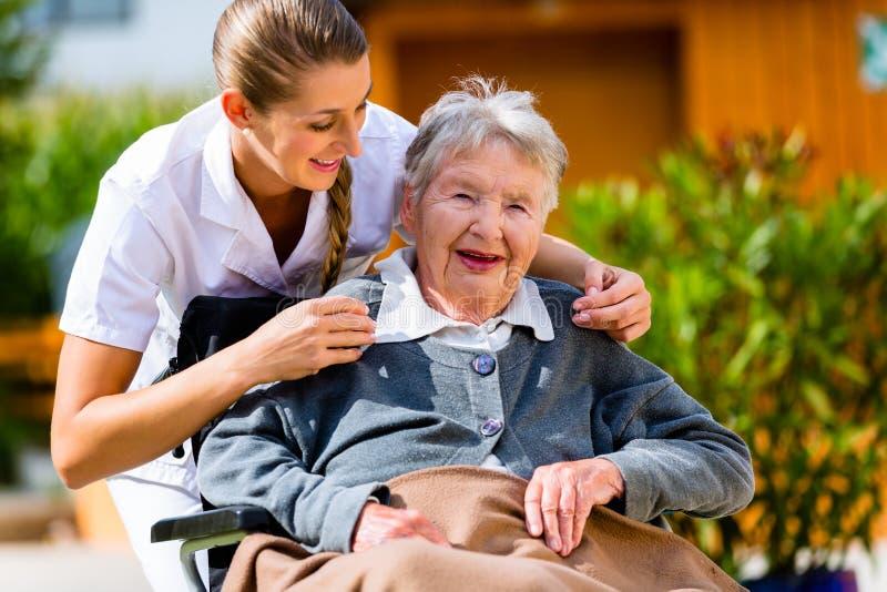 Hogere vrouw in verpleeghuis met verpleegster in tuin stock afbeeldingen