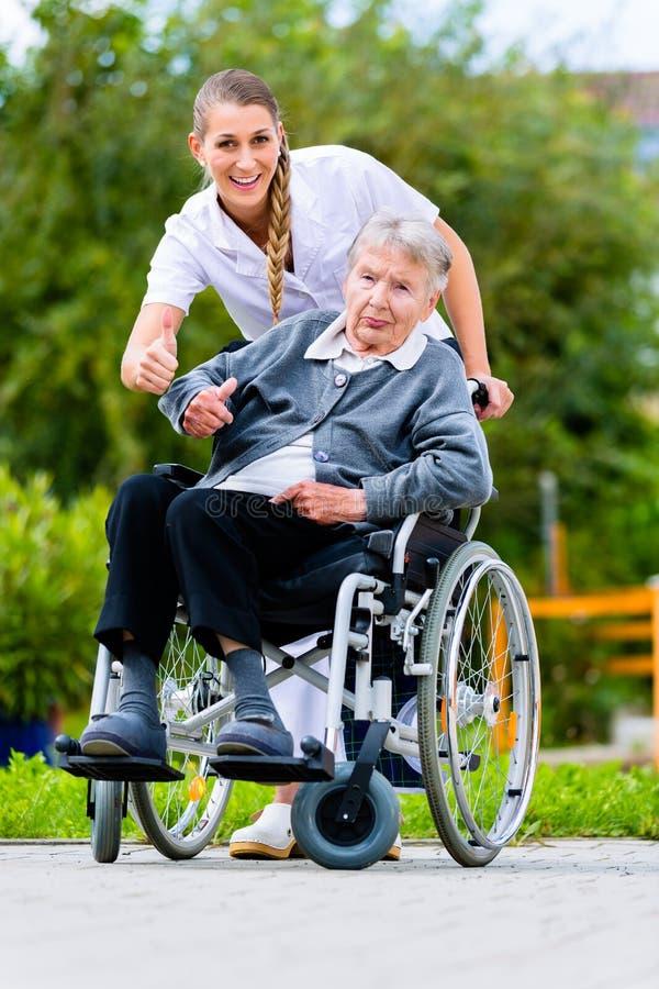 Hogere vrouw in verpleeghuis met verpleegster in tuin stock afbeelding