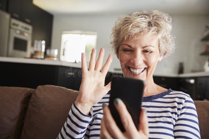 Hogere vrouw video het uitnodigen smartphone thuis, sluit omhoog stock afbeelding