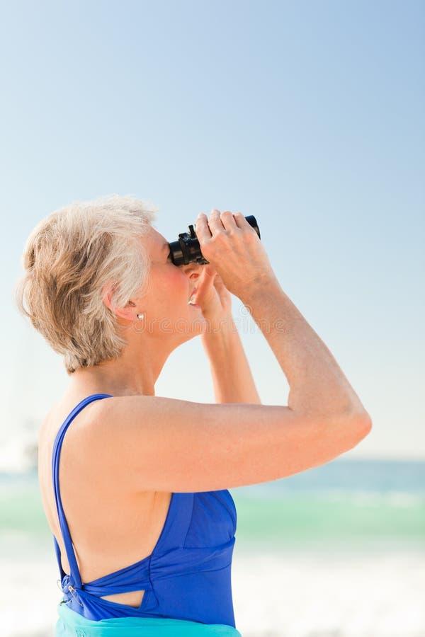 Hogere vrouw vogelwaarneming bij het strand royalty-vrije stock foto's