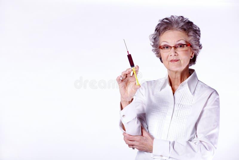 Hogere vrouwelijke arts met spuit royalty-vrije stock afbeelding