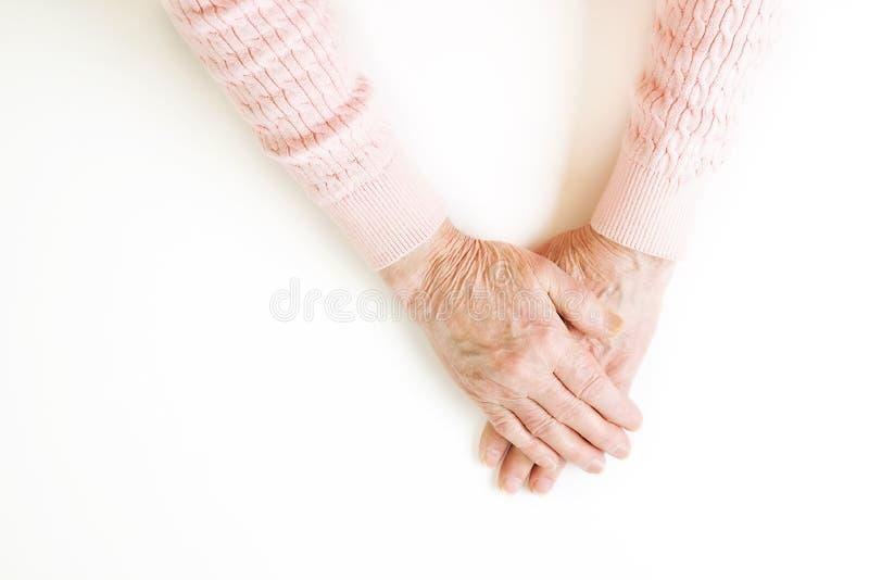 Hogere vrouwelijke die gebaartaal, handentekens op stevige witte achtergrond worden geïsoleerd Oud wijfje in de haar jaren '70/ja stock foto