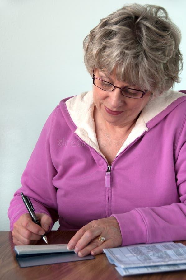 Hogere vrouwelijke het schrijven controle stock foto