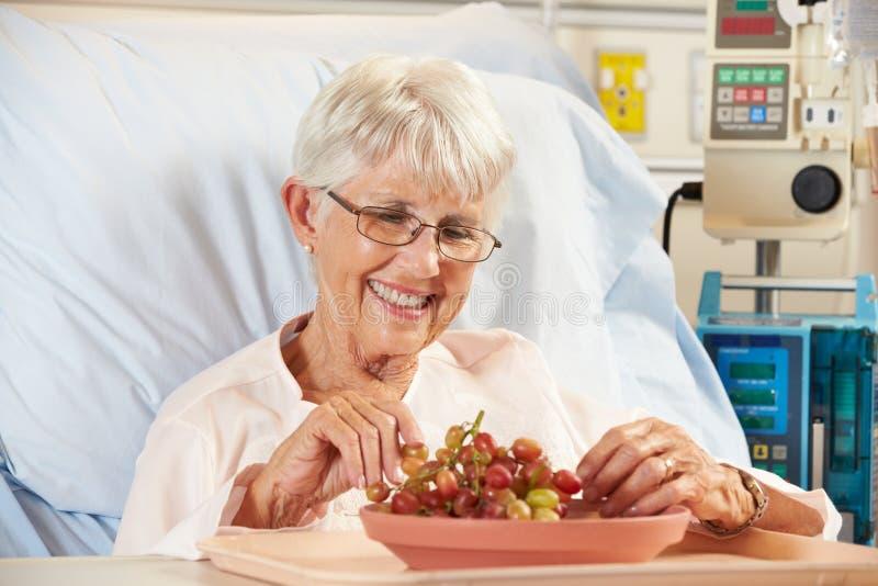 Hogere Vrouwelijke Patiënt die Druiven in het Bed van het Ziekenhuis eten stock foto's