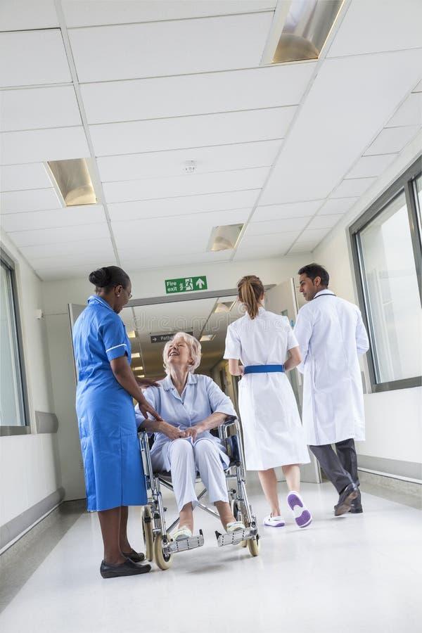 Hogere Vrouwelijke Patiënt in Rolstoel & Verpleegster in het Ziekenhuis stock foto