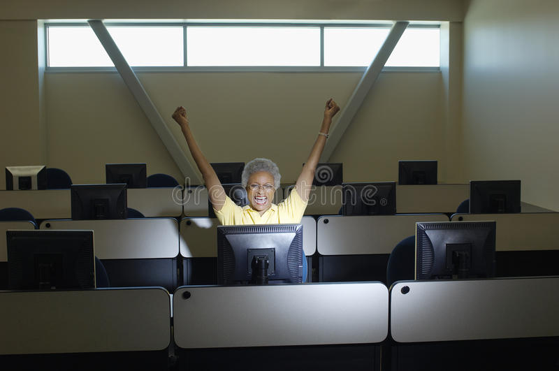 Hogere Vrouwelijke Professor Celebrating Victory In Computer Classroom royalty-vrije stock afbeeldingen