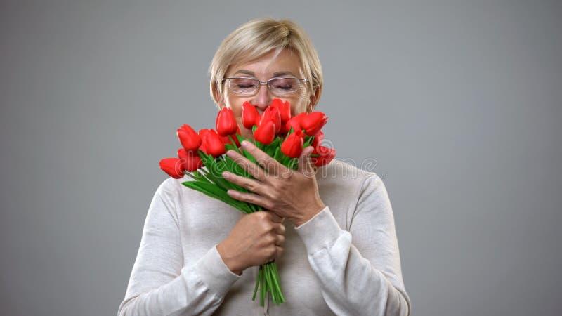 Hogere vrouwelijke ruikende bloemen en het glimlachen op camera, romantische gift, vrouwelijkheid royalty-vrije stock foto's