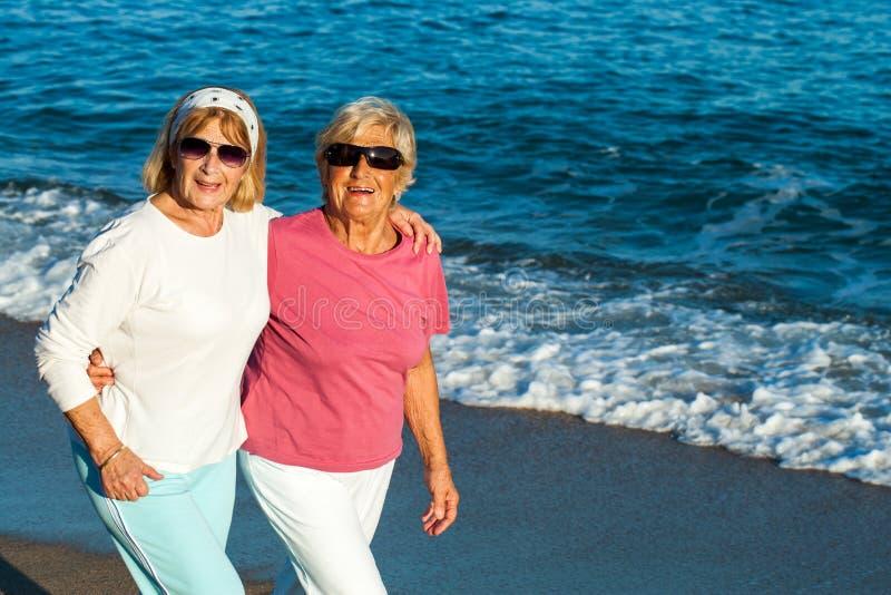Hogere vrouwelijke vrienden die langs het strand lopen. royalty-vrije stock afbeeldingen