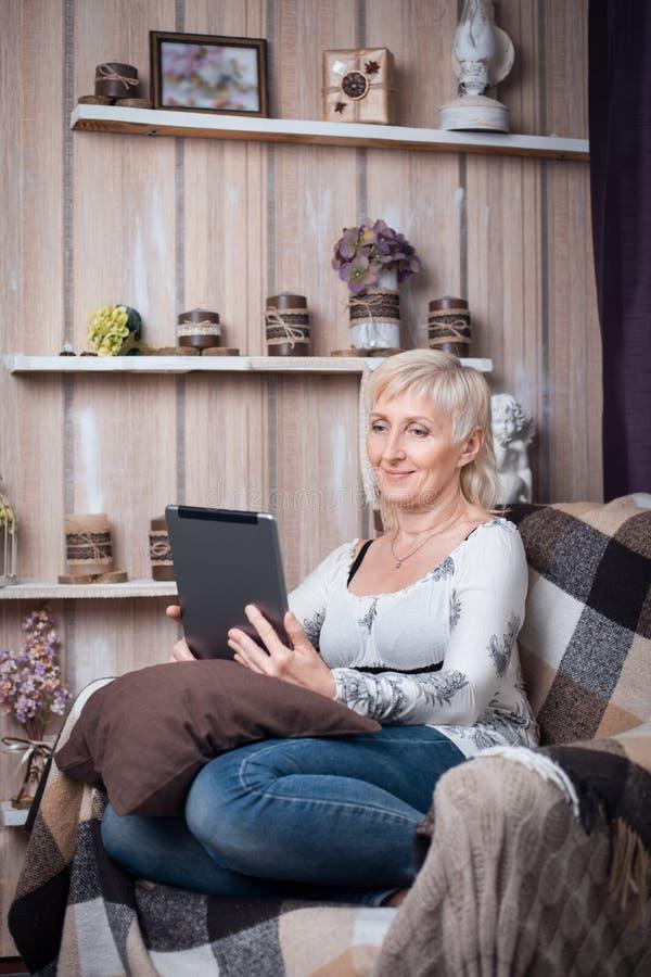 Hogere vrouwelijke zitting in comfortabele ruimte en doorbladerend Internet met Ta stock fotografie