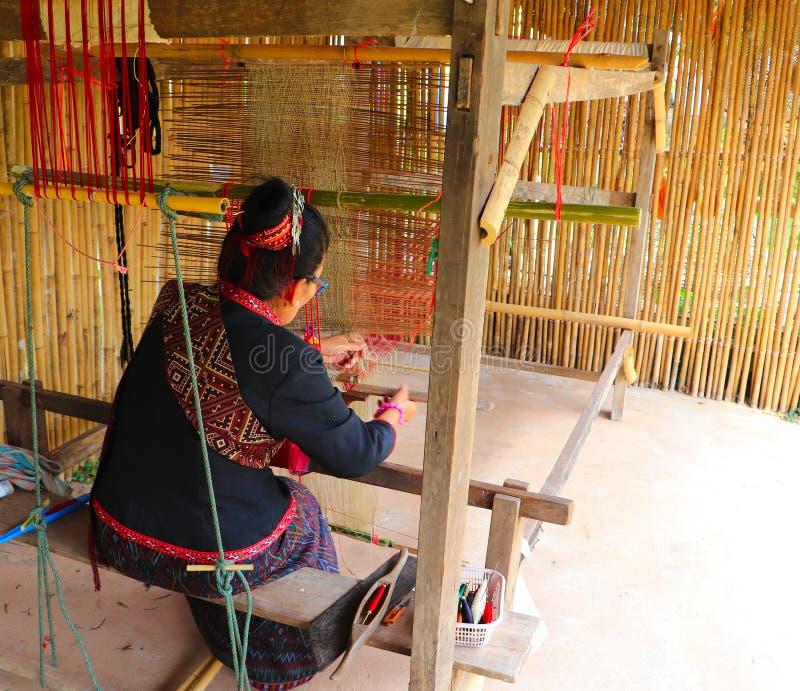 Hogere vrouwen die op houten wevend weefgetouw met kleurrijke patroon textiel en wevende pendel weven royalty-vrije stock fotografie