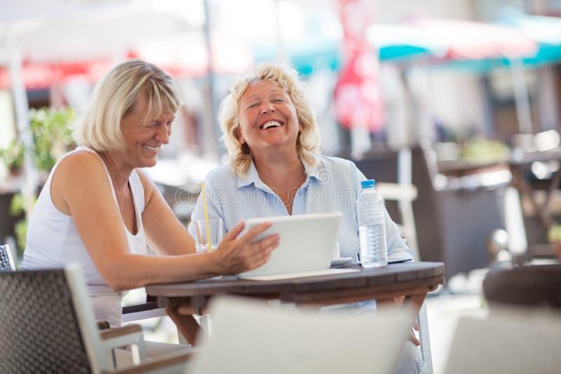 Hogere vrouwen die terwijl binnen het gebruiken van tabletpc lachen royalty-vrije stock afbeelding