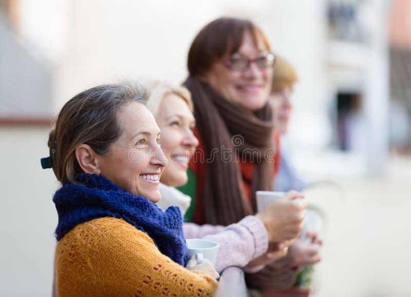 Hogere vrouwen die thee drinken bij balkon stock afbeelding
