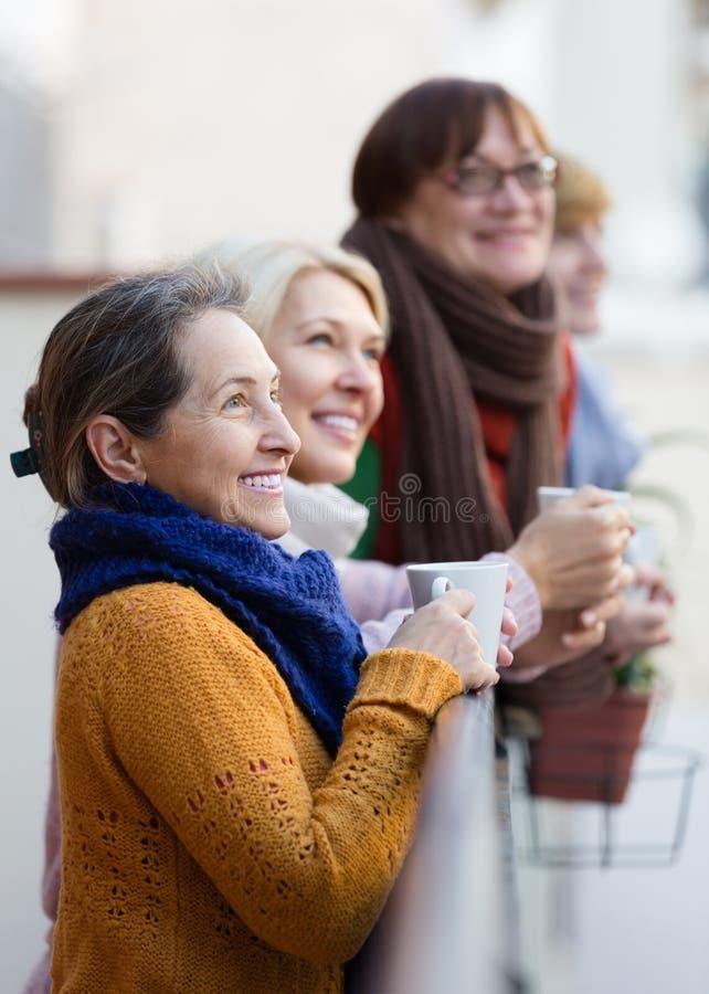 Hogere vrouwen die thee drinken bij balkon royalty-vrije stock foto's