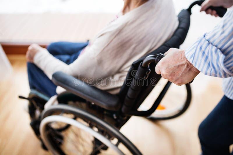 Hogere vrouwen met rolstoel thuis royalty-vrije stock afbeelding