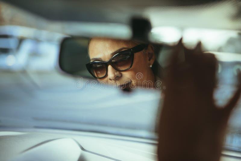 Hogere vrouwenbestuurder die de achterspiegel van de meningsauto aanpassen royalty-vrije stock foto