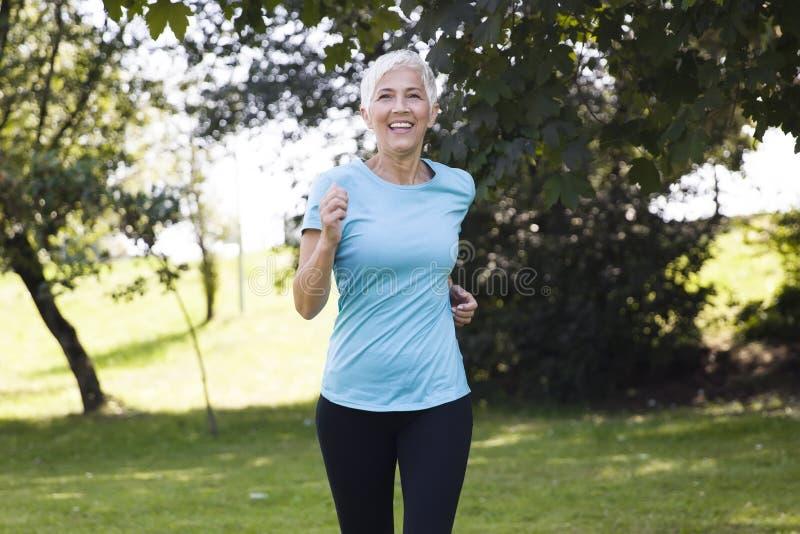 Hogere vrouwenjogging door park stock afbeeldingen