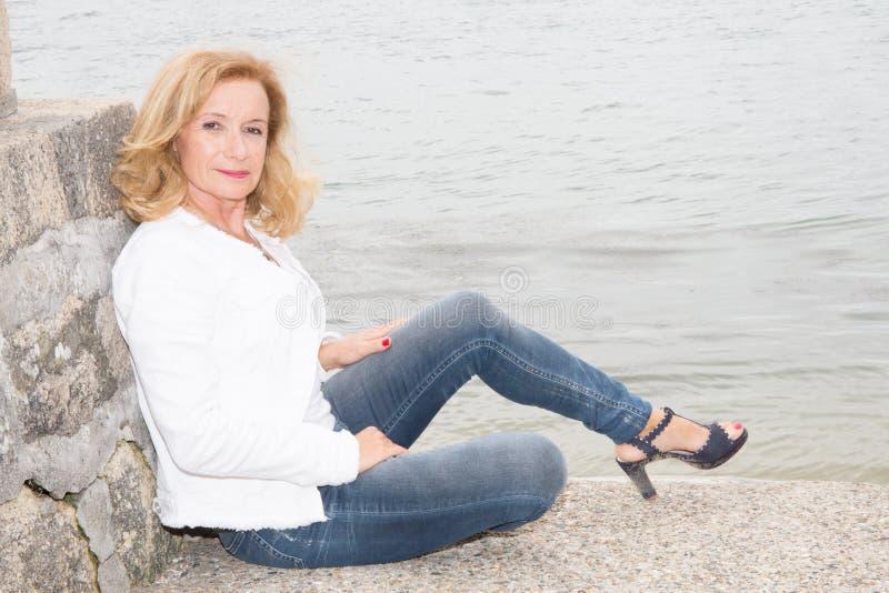 Hogere vrouwenmanier dichtbij strandmeer of overzees stock fotografie