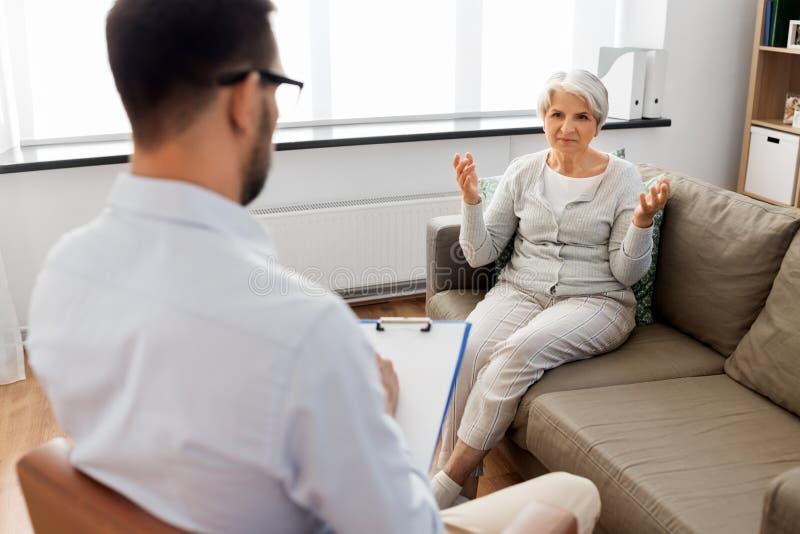 Hogere vrouwenpatiënt die aan psycholoog spreken stock afbeelding