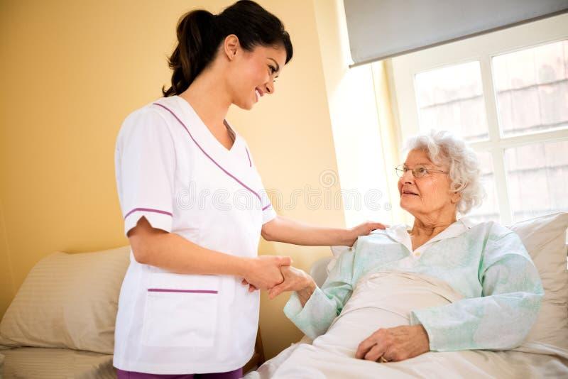 Hogere vrouwenpatiënt met verpleegster bij verpleeghuis royalty-vrije stock foto