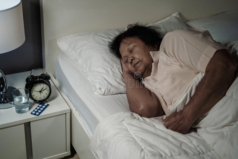 Hogere vrouwenslaap in bed bij nacht stock afbeeldingen