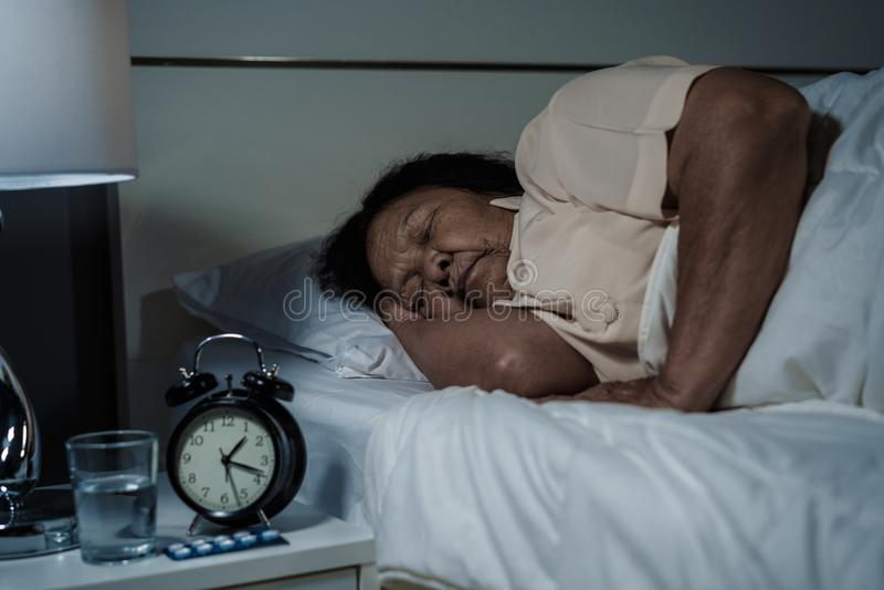 Hogere vrouwenslaap in bed bij nacht stock foto