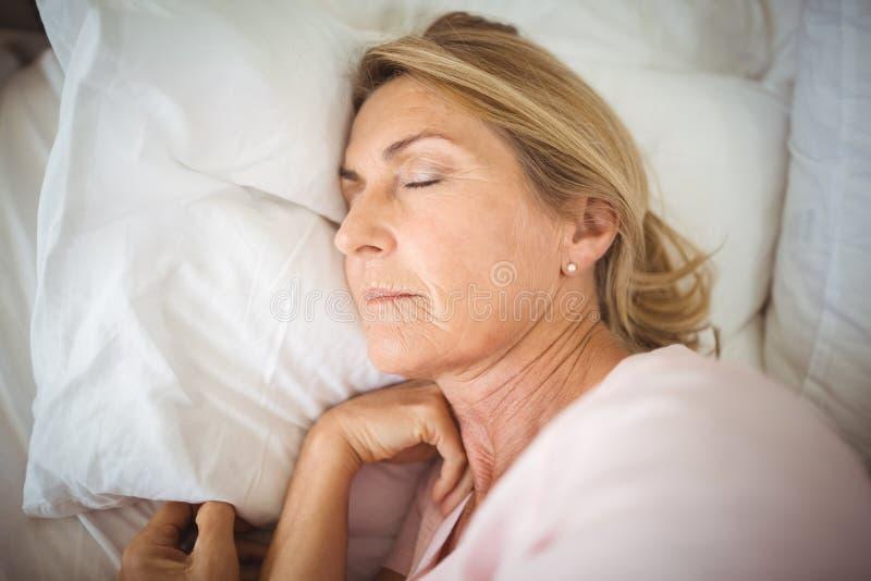 Hogere vrouwenslaap op bed stock afbeeldingen