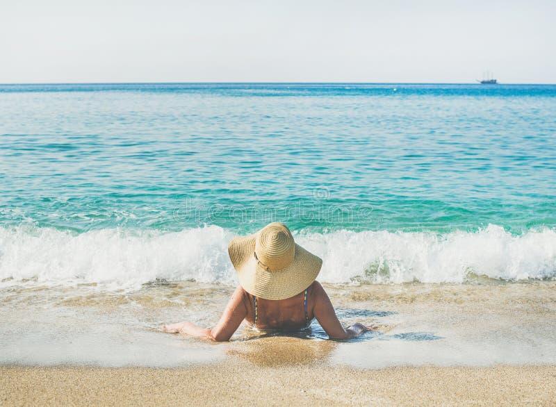 Hogere vrouwentoerist in bikini die op zand liggen die van overzees genieten stock foto