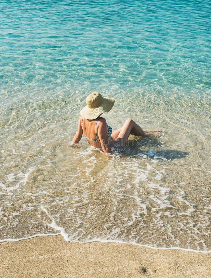 Hogere vrouwentoerist in bikinizitting bij duidelijke zeewaters royalty-vrije stock foto's