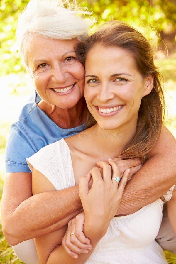 Hogere vrouwenzitting in openlucht met haar volwassen dochter royalty-vrije stock afbeelding