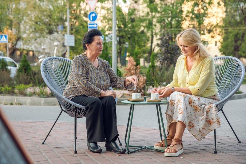 Hogere vrouwenzitting in straatkoffie, het drinken koffie, het spreken, het lachen en het hebben van pret Gelukkige mensen in pen stock afbeelding