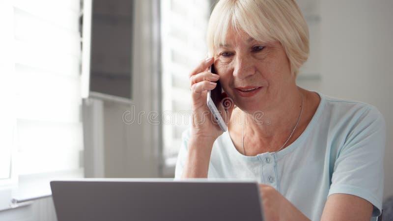 Hogere vrouwenzitting thuis met laptop en smartphone Het bespreken van project op het scherm door cellphone stock afbeelding