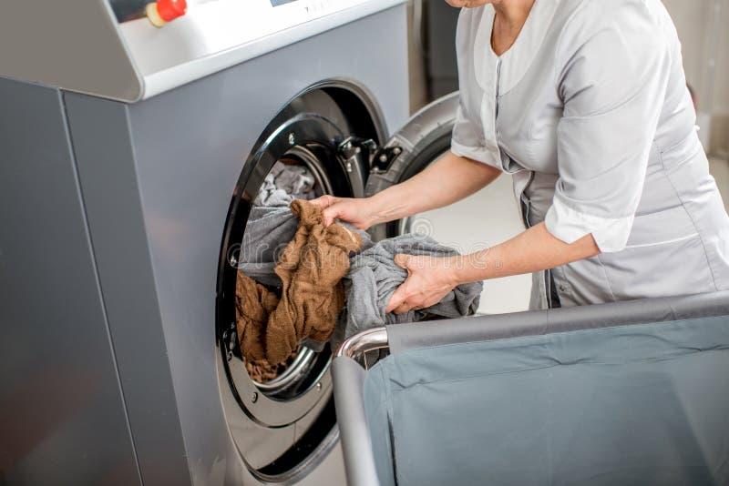 Hogere washwoman in de wasserij stock foto's