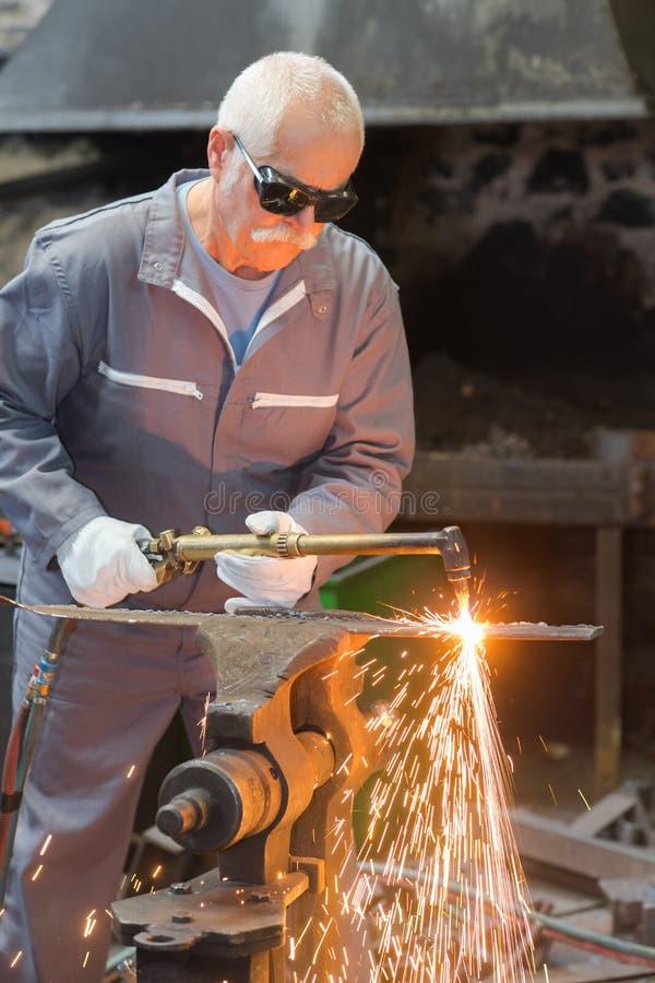 Hogere werkman die met molen werken die flitsfonkelingen veroorzaken stock foto's