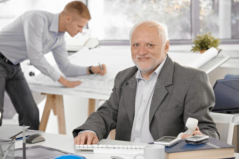 Hogere zakenman die in bureau glimlacht stock fotografie