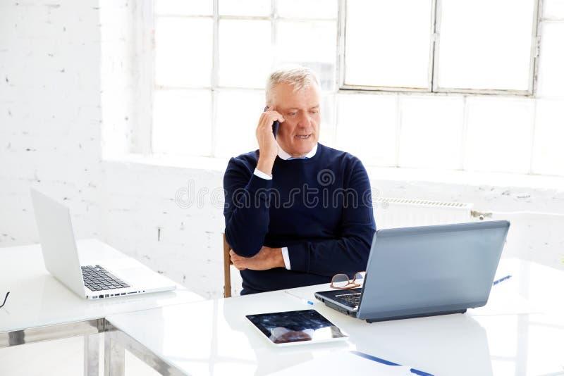 Hogere zakenman die telefoneren terwijl en laptop met behulp van terwijl het werken in het bureau stock afbeeldingen