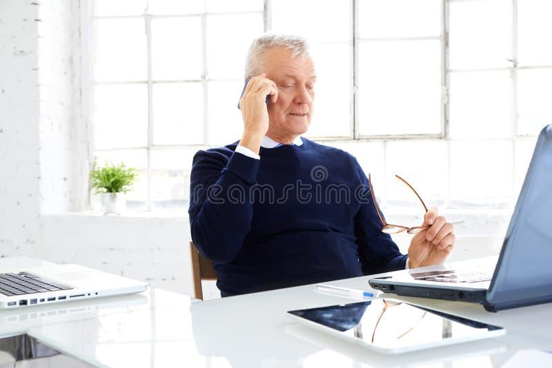 Hogere zakenman die telefoneren terwijl en laptop met behulp van terwijl het werken in het bureau stock foto's