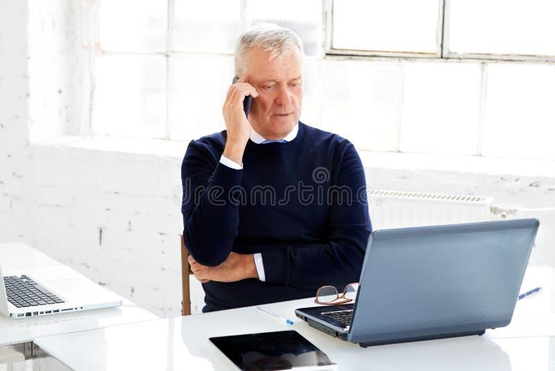 Hogere zakenman die telefoneren terwijl en laptop met behulp van terwijl het werken in het bureau royalty-vrije stock foto's