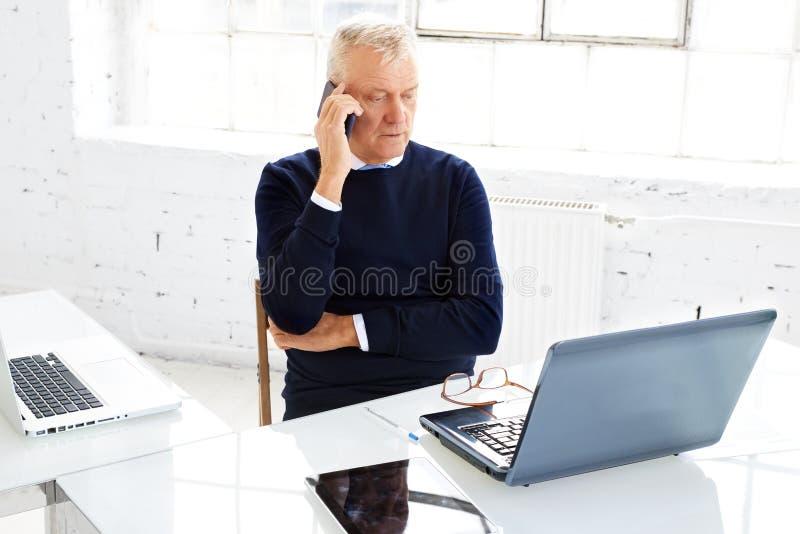 Hogere zakenman die telefoneren terwijl en laptop met behulp van terwijl het werken in het bureau royalty-vrije stock afbeelding