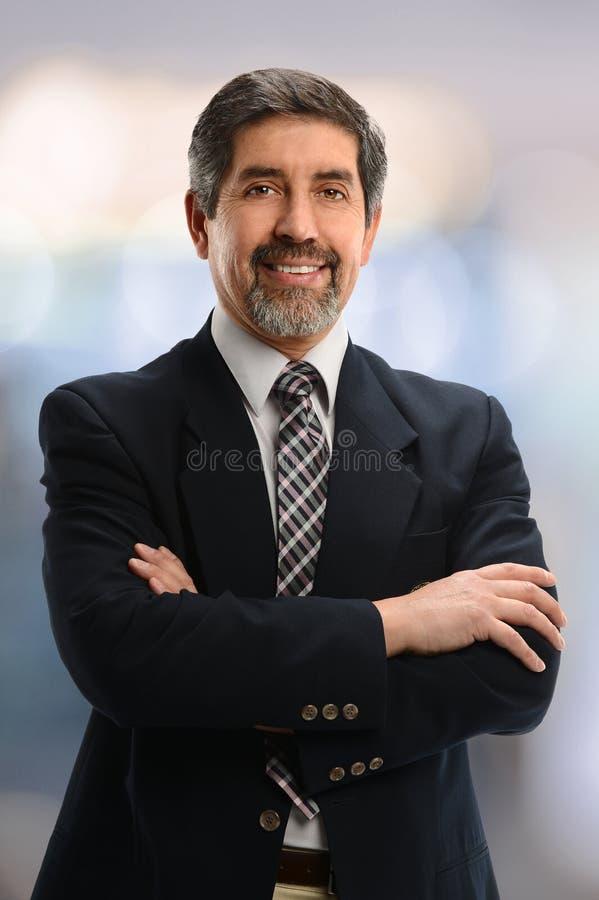 Hogere zakenman met gekruiste wapens stock afbeelding
