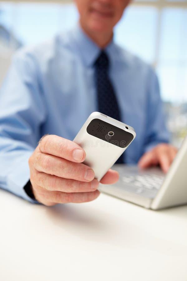 Hogere zakenman met laptop en telefoon royalty-vrije stock afbeelding