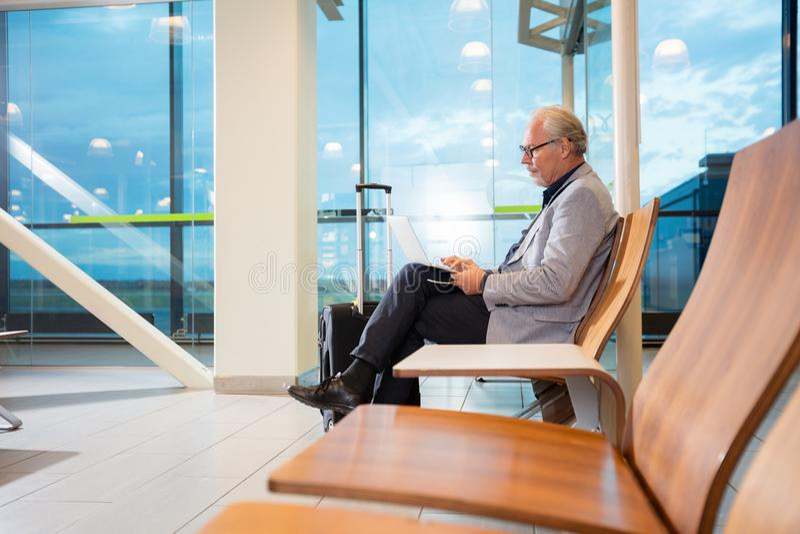 Hogere Zakenman Using Laptop While die op Vlucht wachten royalty-vrije stock fotografie